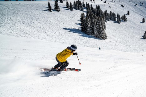 person in green jacket riding on red ski board on snow covered ground during daytime